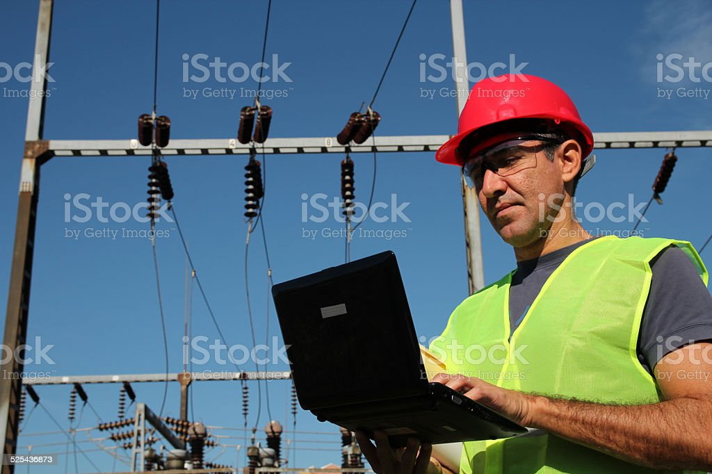 Engineer Using Laptop at an Electrical Substation stock photo