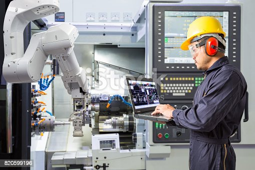 istock Engineer using laptop computer for maintenance automatic robotic arm with CNC machine in smart factory. Industry 4.0 concept 820599196
