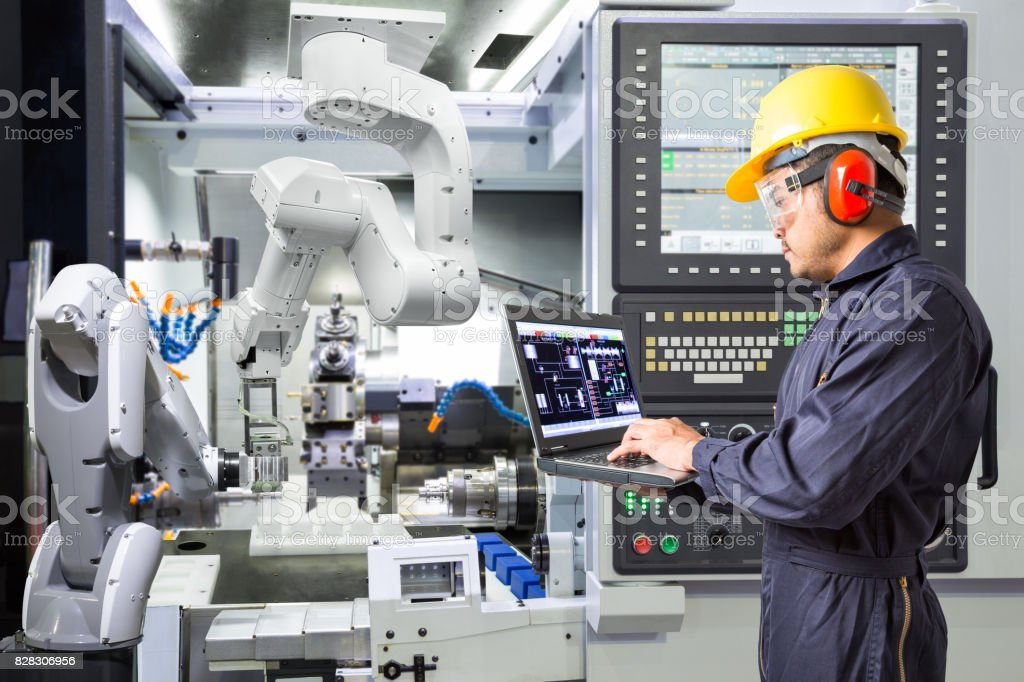 Engineer using laptop computer for maintenance automatic robotic arm with CNC machine in smart factory. Industry 4.0 concept stock photo