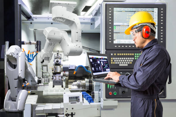 engineer using laptop computer for maintenance automatic robotic arm with cnc machine in smart factory. industry 4.0 concept - robotics manufacturing stock photos and pictures