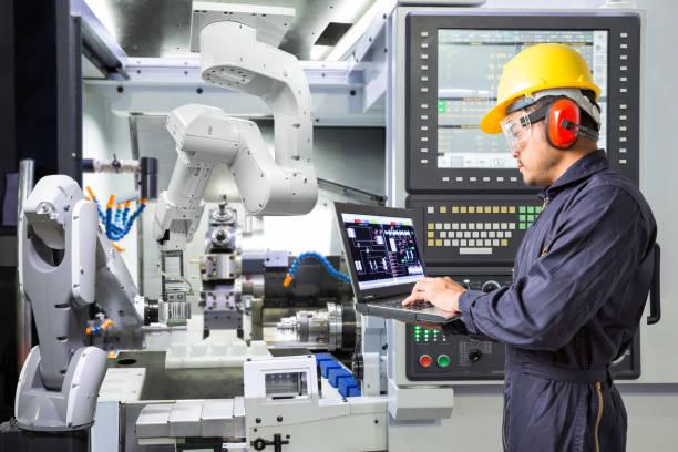 ingenieur met laptopcomputer voor onderhoud automatische robotarm met cnc-machine in slimme fabriek. industrie 4.0 concept - robot engineer stockfoto's en -beelden