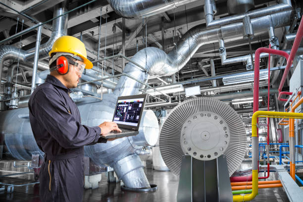 Engineer using laptop computer for maintenance in thermal power stock photo