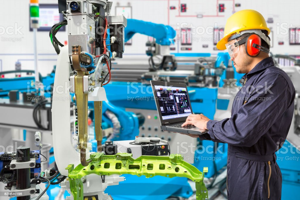 Engineer using laptop computer maintenance automatic robotic hand machine tool in automotive industry manufacturing factory stock photo