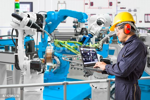 874298574 istock photo Engineer using laptop computer maintenance automatic robotic welding with robot workpiece in automotive industry, Smart factory concept 874298076