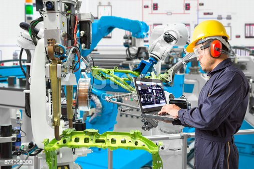 874298574 istock photo Engineer using laptop computer maintenance automatic robotic welding with robot workpiece in automotive industry, Smart factory concept 874298300