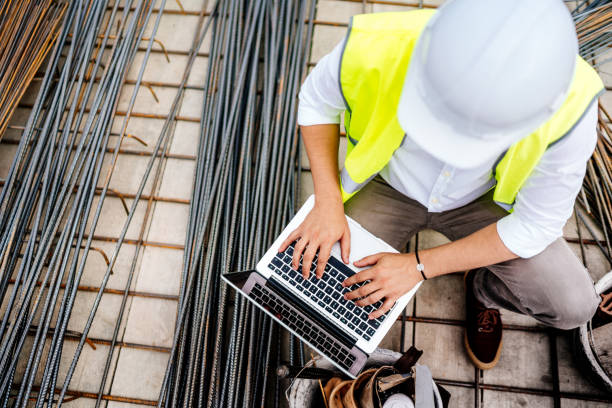 engineer using laptop on construction site. Building industry details stock photo
