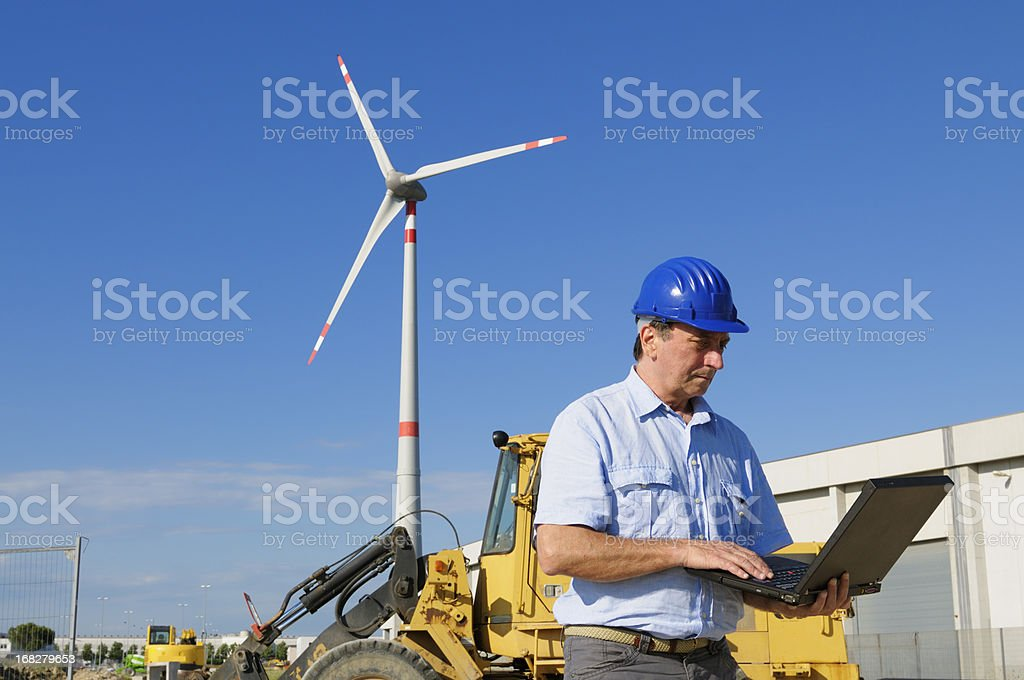 Engineer Using PC in a Wind Turbine Farm stock photo