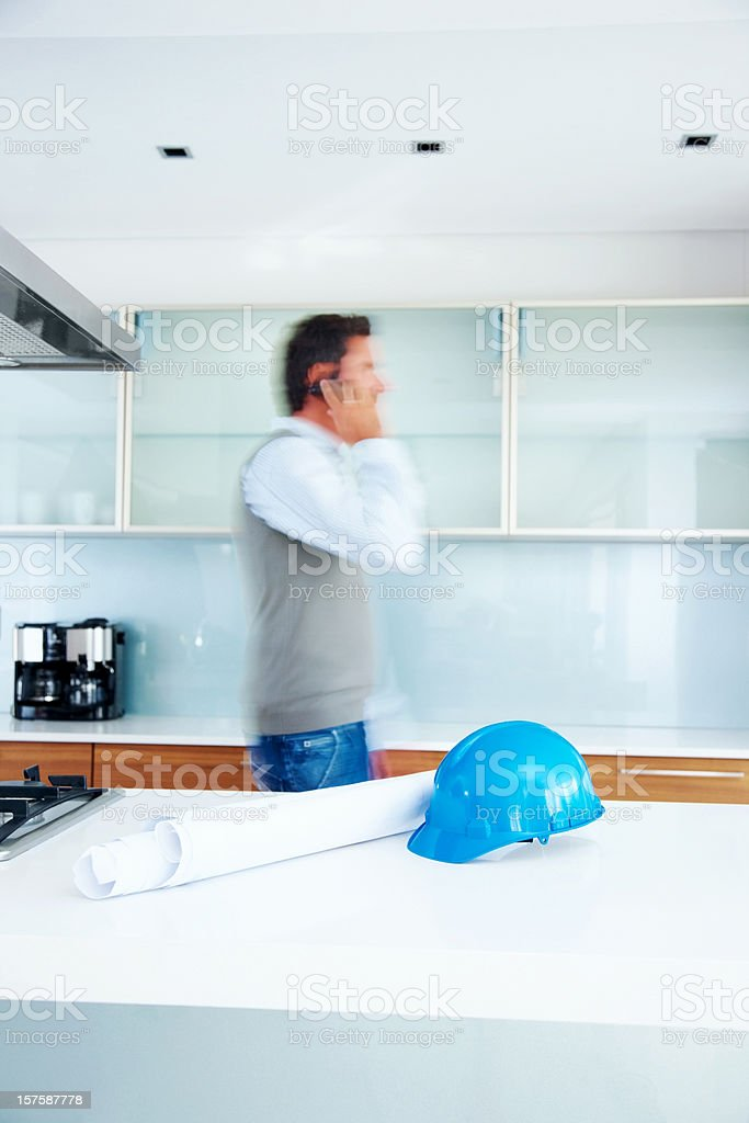 Engineer using phone with blueprints on the table royalty-free stock photo