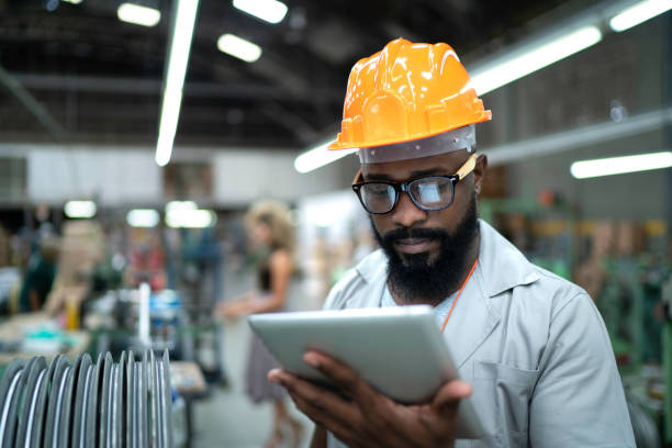 Engineer using tablet and working in factory stock photo