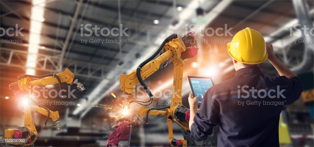 Engineer using tablet check and control automation robot arms machine in intelligent factory industrial on monitoring system software. Welding robotics and digital manufacturing operation. - Royalty-free Adult Stock Photo