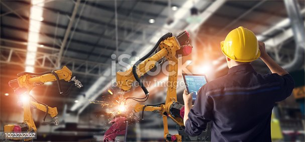 istock Engineer using tablet check and control automation robot arms machine in intelligent factory industrial on monitoring system software. Welding robotics and digital manufacturing operation. 1023232352