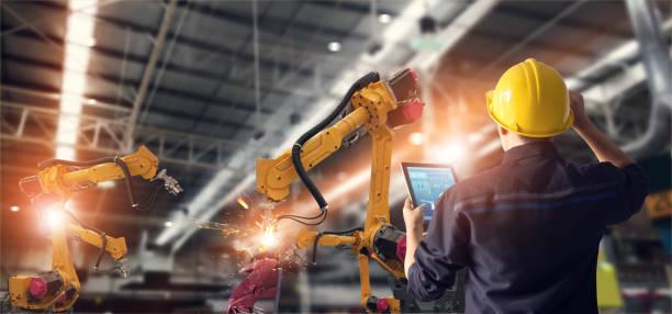 ingeniero utilizando tablet y controlar automatización robot brazos máquina en fábrica inteligente industrial sobre el control de software del sistema. soldadura robótica y operación de fabricación digital. - robot fotografías e imágenes de stock