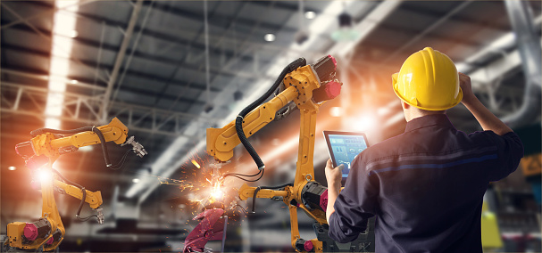 Engineer Using Tablet Check And Control Automation Robot Arms Machine In Intelligent Factory Industrial On Monitoring System Software Welding Robotics And Digital Manufacturing Operation Stock Photo - Download Image Now