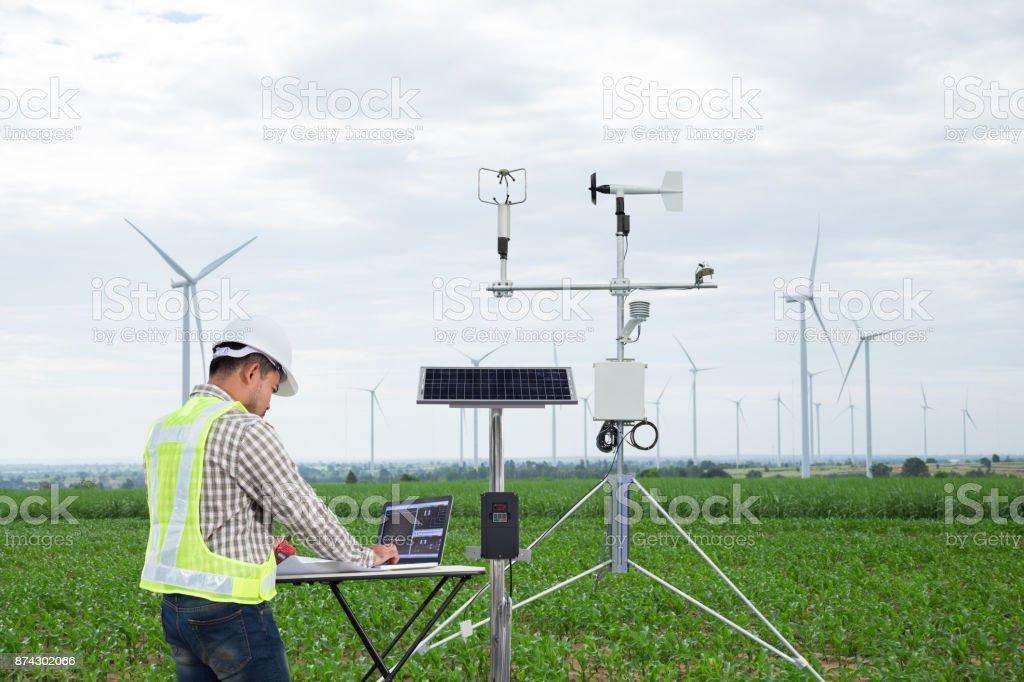 工程師使用平板電腦收集資料用氣象儀器測量風速、溫濕度和太陽電池系統的玉米田背景, 智慧農業技術概念 - 免版稅器材圖庫照片