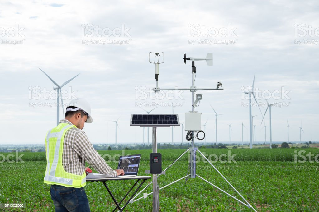 Engineer using tablet computer collect data with meteorological instrument to measure the wind speed, temperature and humidity and solar cell system on corn field background, Smart agriculture technology concept stock photo