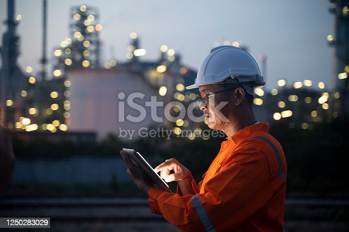 Engineer using tablet near oil refinery at night.