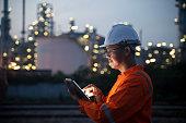 istock Engineer using tablet near oil refinery at night. 1250283029