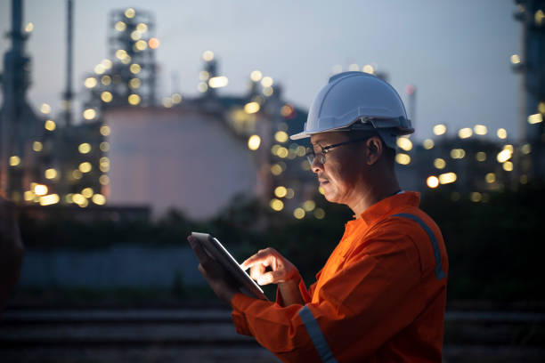 Engineer using tablet near oil refinery at night. stock photo