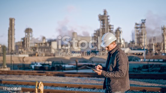 istock Engineer using tablet near oil refinery industry. 1216409645