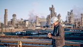Waist up shot of an engineer in a white hardhat using a tablet with an oil refinery visible in the background.