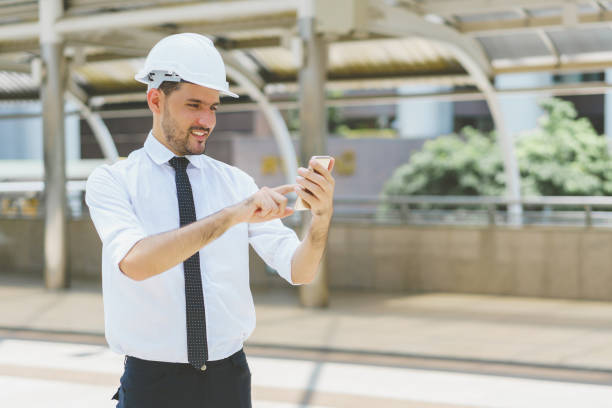 Engineer wearing safety helmet and touching smartphone with smile at construction site. concept of communication and negotiation. stock photo