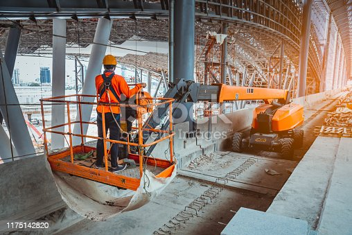 istock A Engineer wearing safety uniform and safety helmet ,controlling straight Boom Lift to construction roof on sky rail train platform station . 1175142820