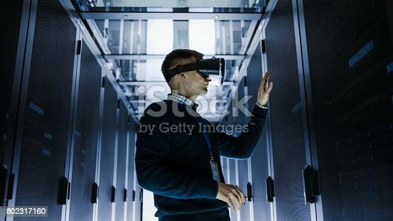 802303638istockphoto IT Engineer Wearing Virtual Reality Headset Works with Augmented Reality Software in Data Center. He Wirelessly Interacts with Rack Servers. 802317160