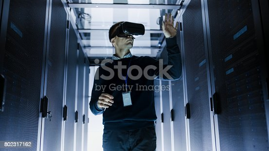 802317162istockphoto IT Engineer Wearing Virtual Reality Headset Works with Augmented Reality Software in Data Center. He Wirelessly Interacts with Rack Servers. 802317162