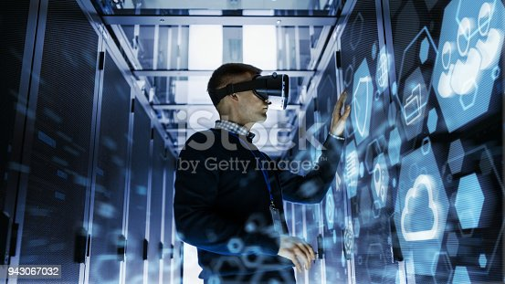 802303638istockphoto IT Engineer Wearing Virtual Reality Headset Works with Augmented Reality Software in Data Center. He Wirelessly Interacts with Rack Servers. 943067032