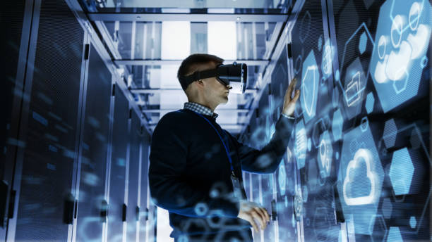 it engineer wearing virtual reality headset works with augmented reality software in data center. he wirelessly interacts with rack servers. - realtà aumentata foto e immagini stock