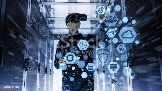 802303638istockphoto IT Engineer Wearing Virtual Reality Headset Works with Augmented Reality Software in Data Center. He Wirelessly Interacts with Rack Servers by Icon Visualization. 943067246