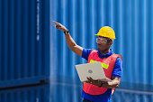 istock Engineer with clipping path in hard hat and safety vest holding a laptop, Factory worker man at container cargo 1269622512