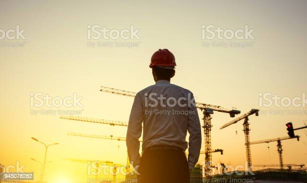 Engineer with crane background at sunset picture id945078282?b=1&k=6&m=945078282&s=612x612&h=lvsmpawogpfqslg3o66uwwjqxduzurgxsmxwogc4imq=