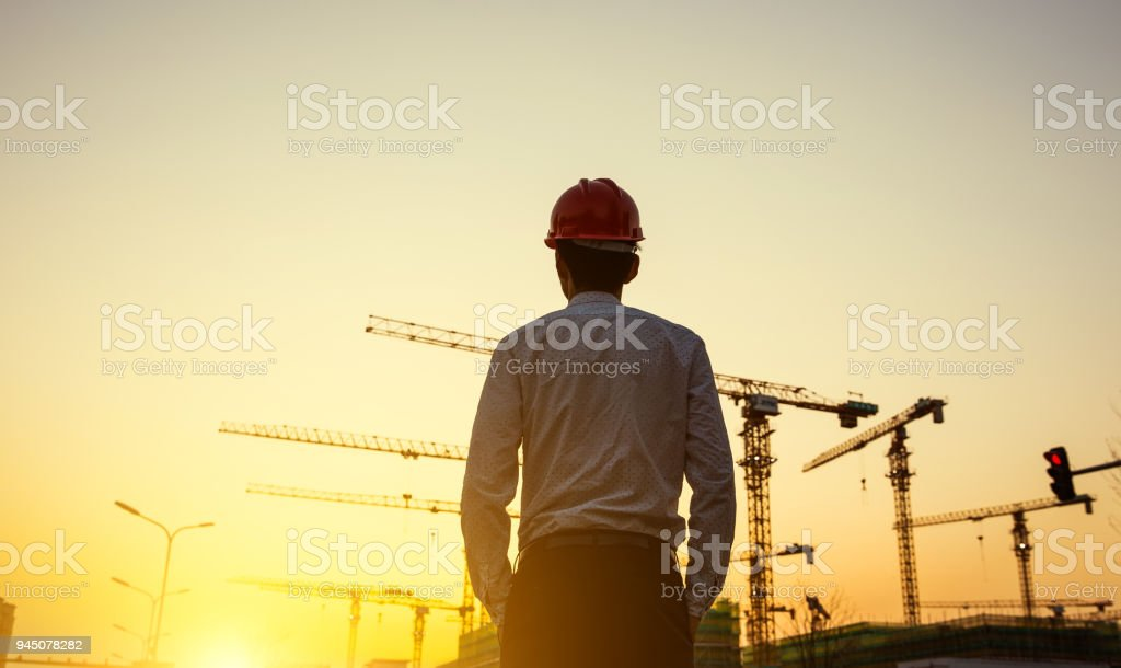 Engineer with crane background at sunset stock photo