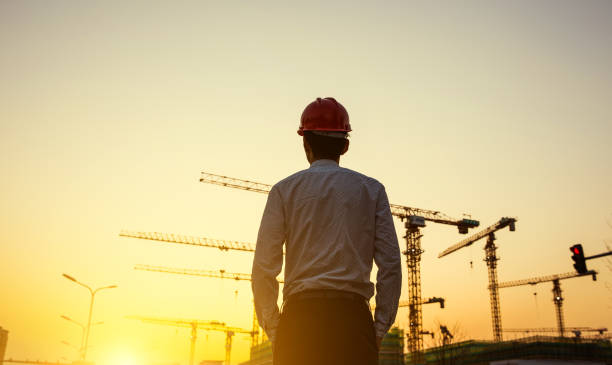 Engineer with crane background at sunset Engineer with crane background at sunset foreman stock pictures, royalty-free photos & images