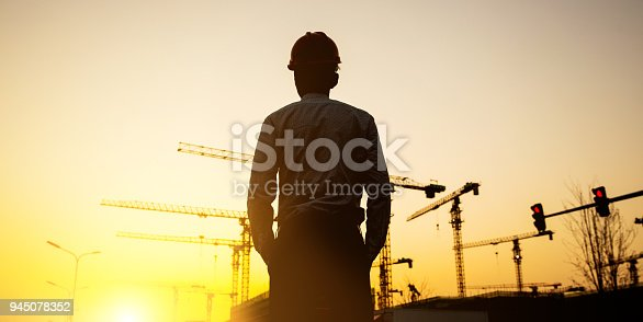 istock Engineer with crane background at sunset 945078352