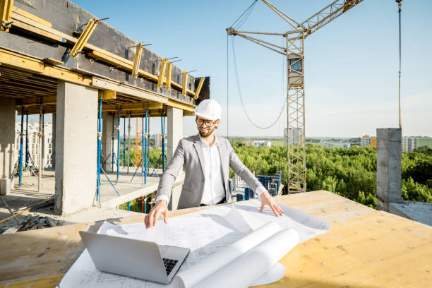 Engineer with drawings on the structure Handsome engineer working with architectural drawings at the table on the construction site outdoors general military rank stock pictures, royalty-free photos & images