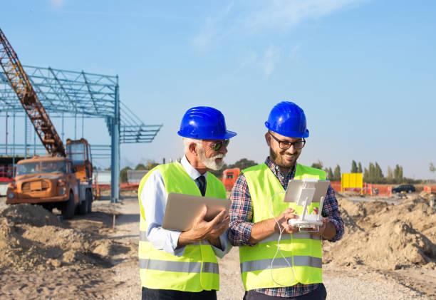 建築現場でドローンを使ったエンジニア - リモート ストックフォトと画像