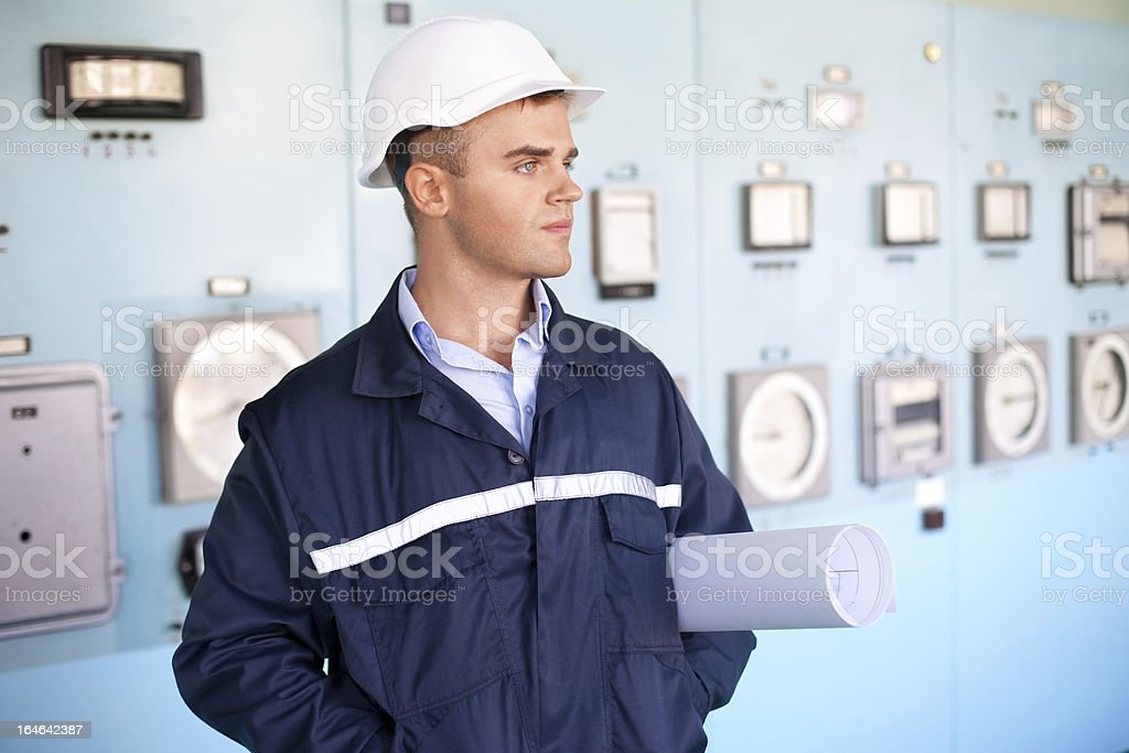 engineer with helmet and blueprints in control room royalty-free stock photo