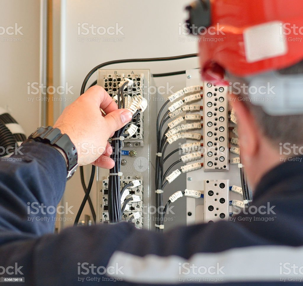 Engineer with Red Hardhat Testing Equipment stock photo
