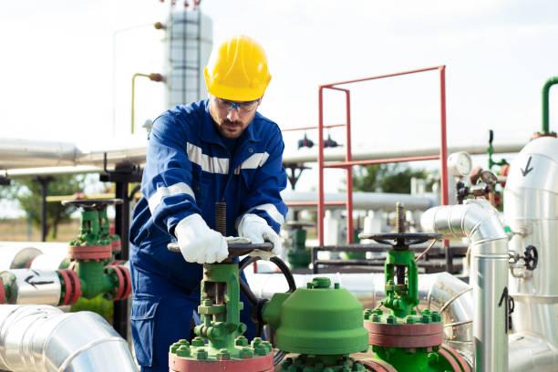 ingenieur mit raffinerie ausrüstung - petrochemische fabrik stock-fotos und bilder