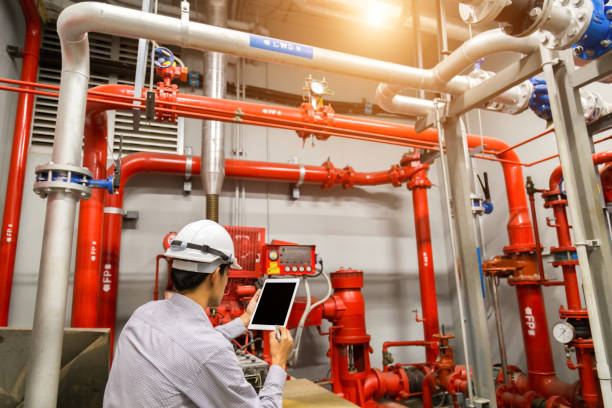 Engineer with tablet check red generator pump for water sprinkler piping and fire alarm control system. Engineer with tablet check red generator pump for water sprinkler piping and fire alarm control system. fire hydrant stock pictures, royalty-free photos & images