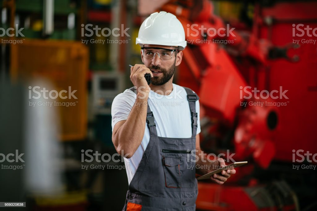 Engineer with walkie-talkie. Shallow DOF. Developed from RAW;...