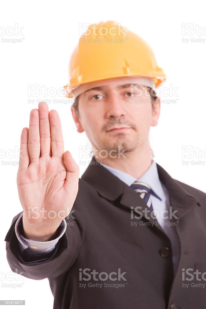 Engineer with yellow hat making stop sign stock photo