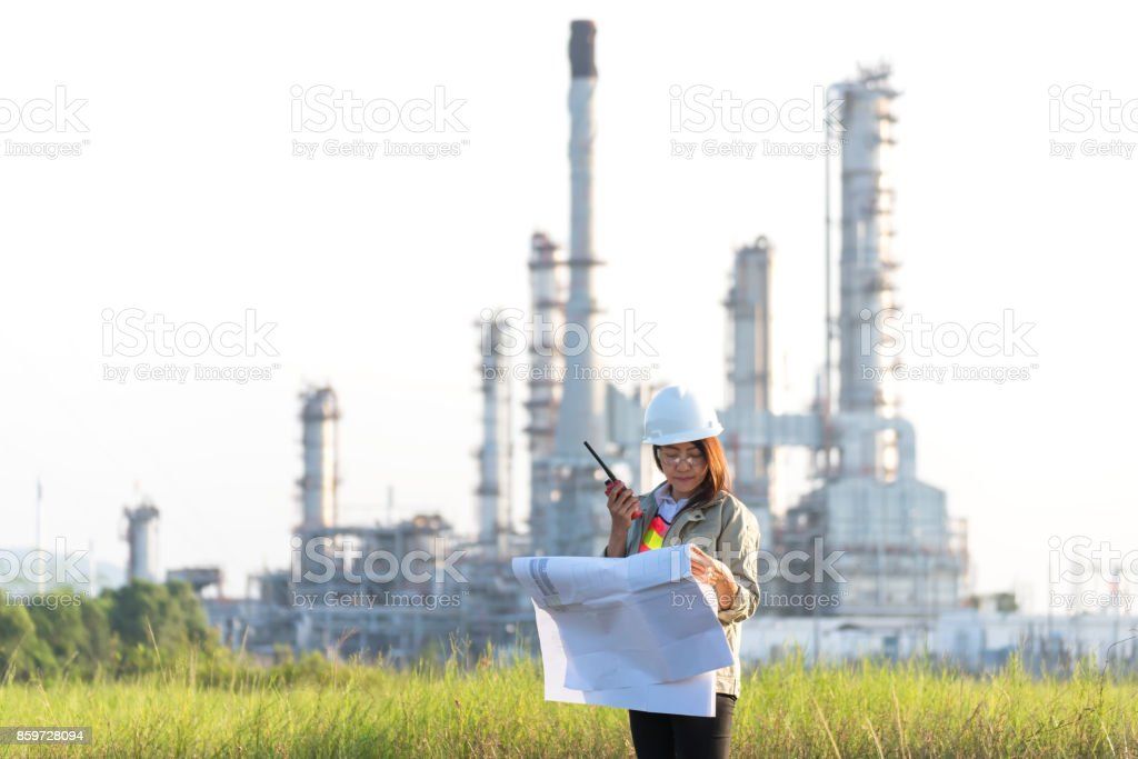 Engineer woman holding blueprint with radio for workers security control at power plant energy and petrochemical industry. Engineer Concept stock photo