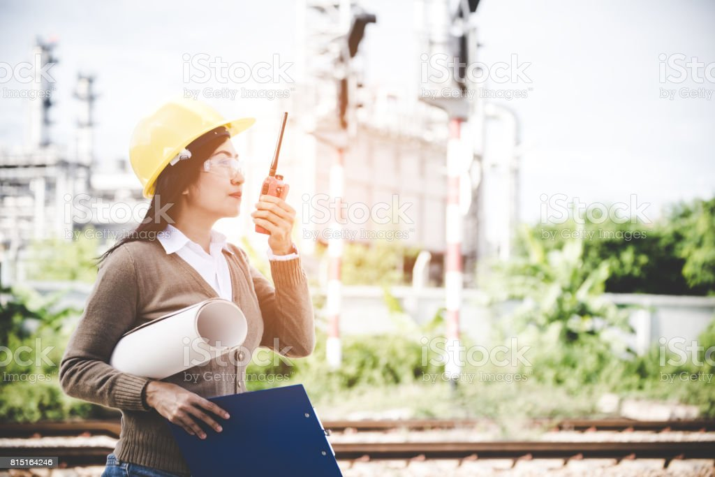 Engineer woman holding radio, blueprint and report schedule for workers security control at power plant energy industry. Engineer Concept stock photo