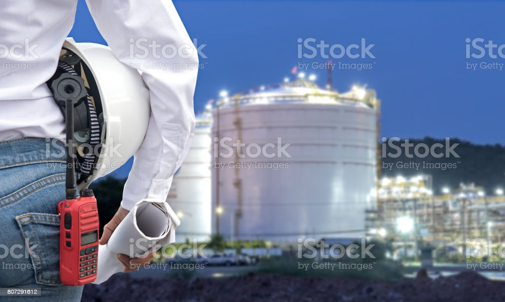 Engineer woman holding white helmet and blueprint with radio for workers security control at power plant energy industry. Engineer Concept stock photo