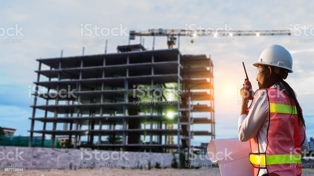 Engineer woman holding white helmet and blueprint with radio for workers . Engineer Concept stock photo