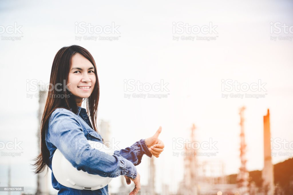 Engineer woman holding white helmet for workers security control at power plant energy industry. Engineer Concept stock photo