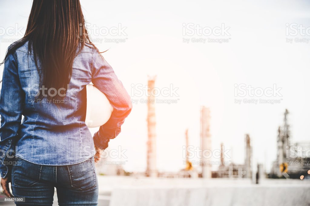 Engineer woman holding white helmet for workers security control at power plant energy industry.  Petrochemicals Plant Background.  Engineer Concept stock photo